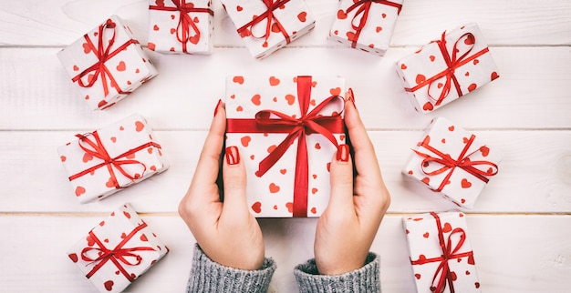 Woman hands give wrapped  holiday gift box