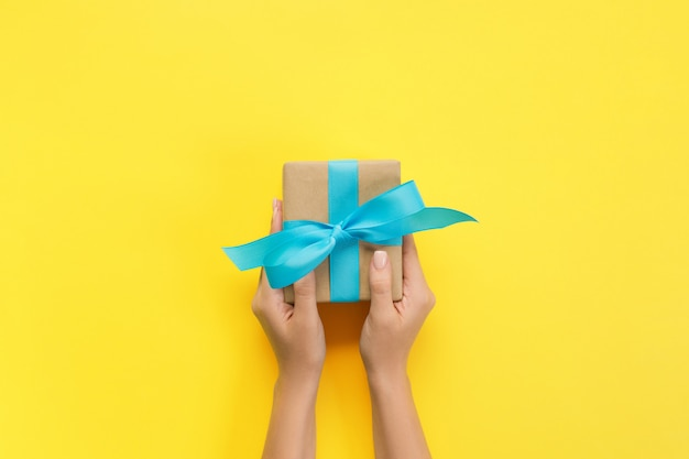 Woman hands give wrapped valentine or other holiday handmade present in paper with blue ribbon. present box, decoration of gift on yellow table, top view with copy space