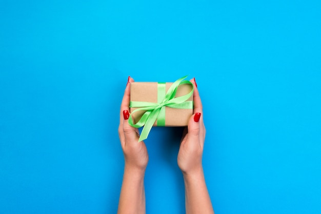 Woman hands give wrapped valentine or other holiday handmade present in paper with green ribbon.
