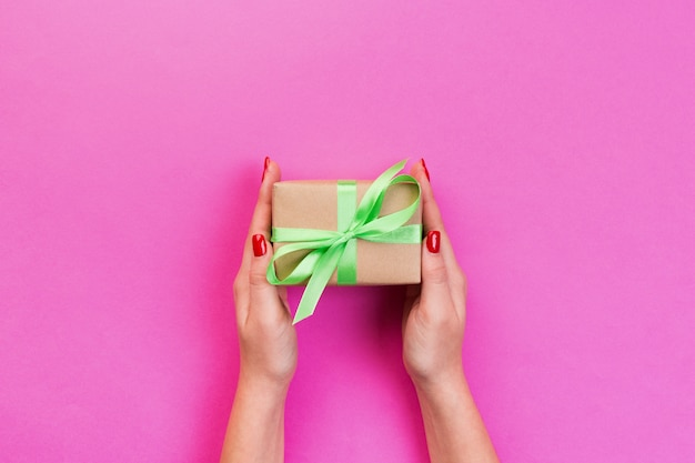 Woman hands give wrapped valentine or other holiday handmade present in paper with green ribbon