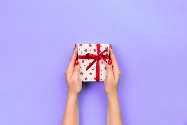 Woman hands give wrapped valentine or other holiday handmade present in paper with red ribbon.