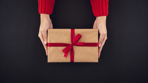 Woman hands giving christsmas gift box top view on black background
