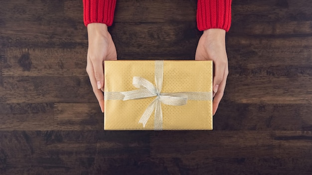 Woman hands giving a christsmas gift box top view on wood table