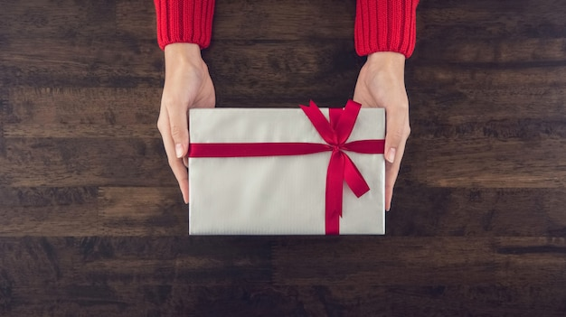 Woman hands giving christsmas gift box wrapped with gray paper