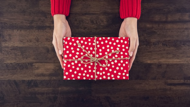 Woman hands giving christsmas gift box wrapped with red dotted paper top view