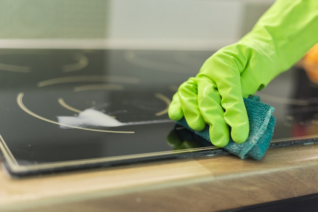 Woman hands in gloves cleans kitchen electric ceramic hob with sponge and detergent