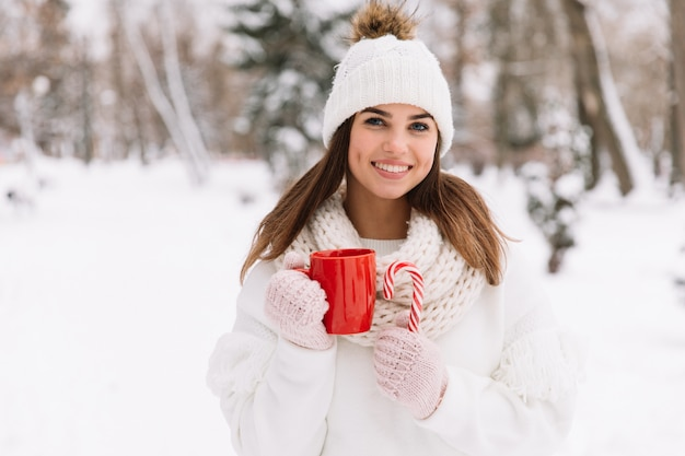 Woman hands in gloves holding a cozy mug with hot cocoa, tea or coffee and a candy cane.