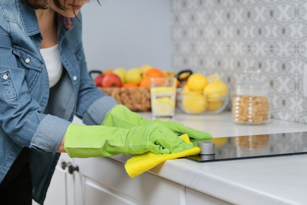 Woman hands in gloves washing and cleaning electric hob in kitchen