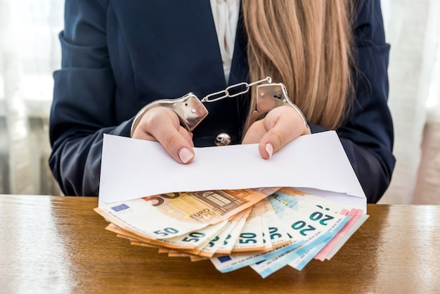 Woman hands in handcuffs with euro notes in envelope