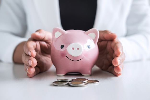 Woman hands having a protective gesture of a piggy bank for planning step up growing to profit