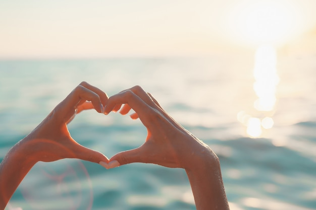 Woman hands in heart shape at blue sea