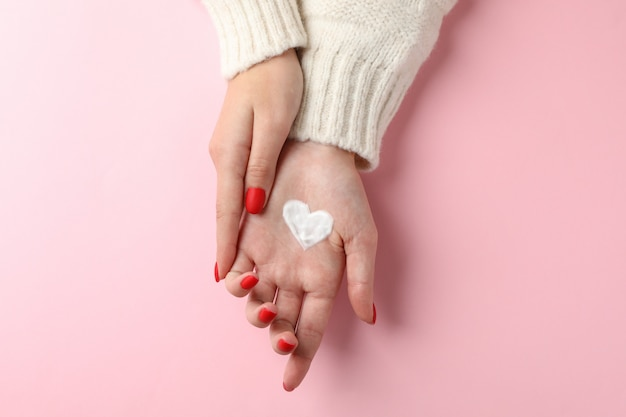 Woman hands, heart shape created from winter cream on pink background. top view