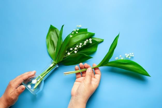 여성의 손은 투명한 유리 꽃병과 작은 나뭇가지에 은방울꽃 꽃다발을 들고 있습니다...