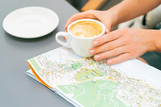 Руки женщины держат чашку кофе на карте на столе. девушка путешествует по канарским островам и ищет новое место для посещения. солнечный день в уличном кафе.