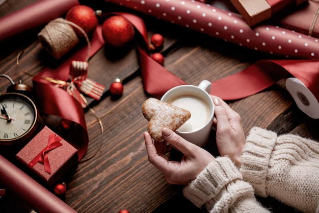 Woman hands hold cup of coffee and cookie on wooden table in wrapping time