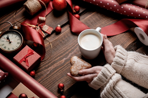 Woman hands hold cup of coffee on wooden table in wrapping time