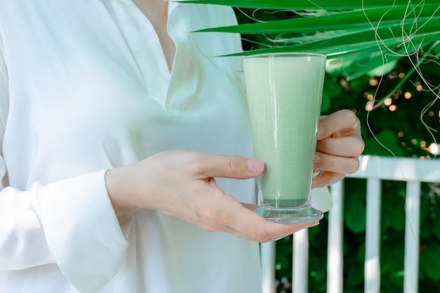 Женские руки держат чашку зеленого маття латте кофе чай стакан зелень листья