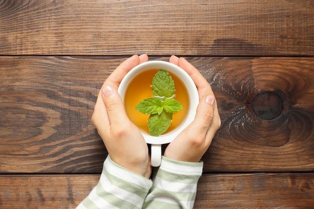 女性の手はミントとお茶のカップを保持し、茶色の木製テーブルの背景に上面図を残します