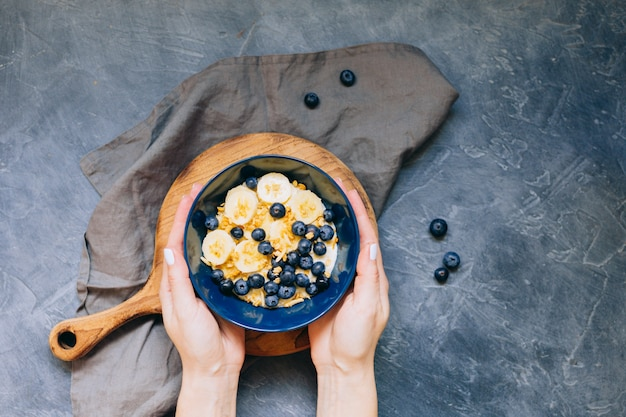 Woman hands hold dark blue bowl of oatmeal porridge with banana and blueberry on vintage table top view in flat lay style. hot breakfast and homemade food. free space. homemade cuisine.