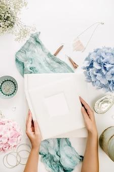 女性の手は家族の結婚式の写真アルバム、パステルカラーのカラフルなアジサイの花の花束、ターコイズブルーの毛布、装飾、白い表面のファッションアクセサリーを保持します