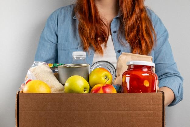 女性の手が果物、シリアル、水、さまざまな缶詰食品の食品募金箱を保持しています。
