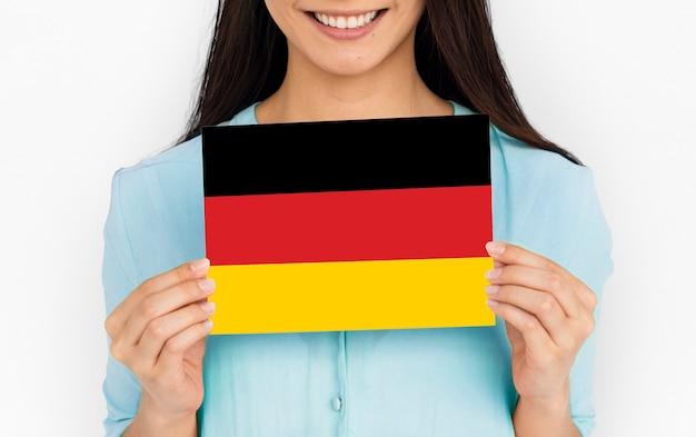 女性の手はドイツを保持しますドイツの旗愛国心