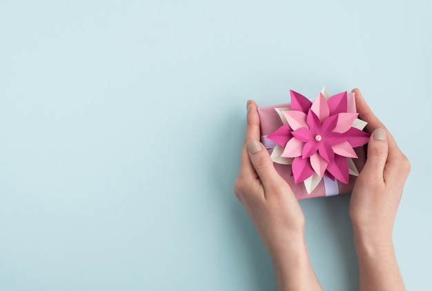Woman hands hold gift box with paper flower bow