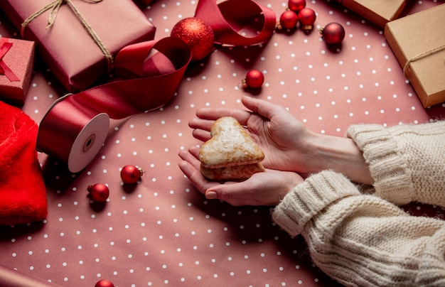 Woman hands hold gingerbread cookie near gifts on wrapping paper