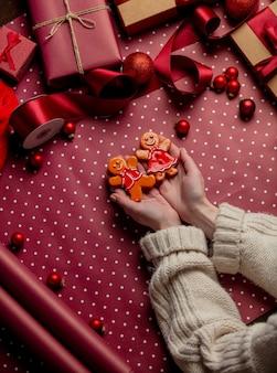 女性の手は、包装紙の贈り物の近くにジンジャーブレッドマンクッキーを保持します