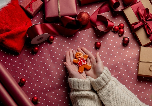 Woman hands hold gingerbread man cookie near gifts on wrapping paper