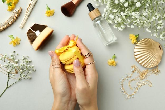 Женские руки держат миндальное печенье на светло-сером фоне с женскими аксессуарами