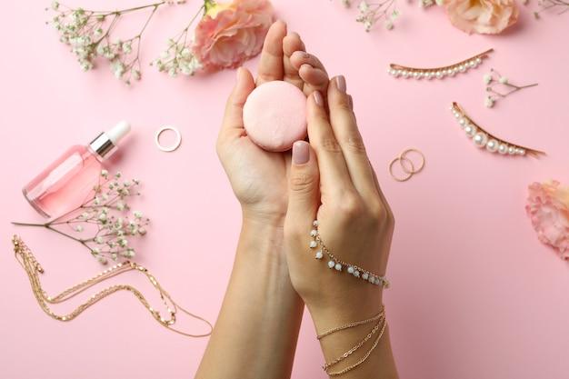 Женские руки держат миндальное печенье на розовом фоне с женскими аксессуарами