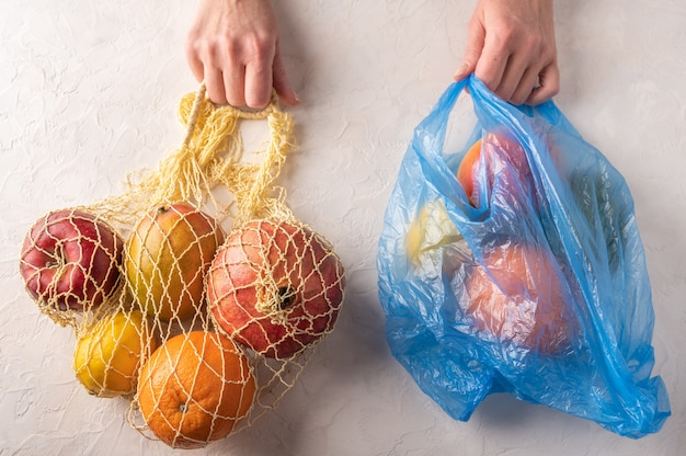 Woman hands hold mixed organic fruit, vegetables and greens in a string bag and plastic on light background.
