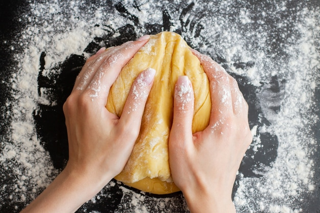 Woman hands hold prepared dough on black table