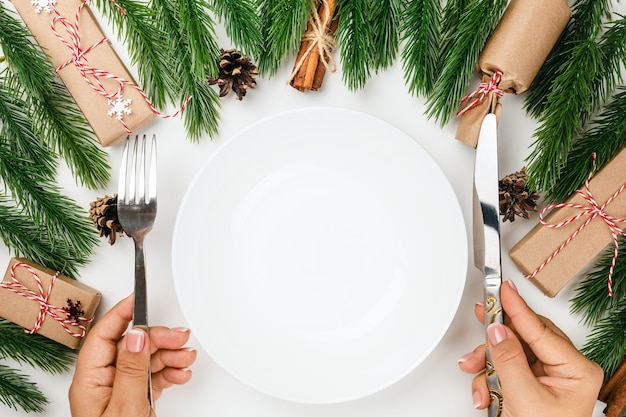 Woman hands hold silver cutlery next to empty white plate framed with christmas tree branches and de...