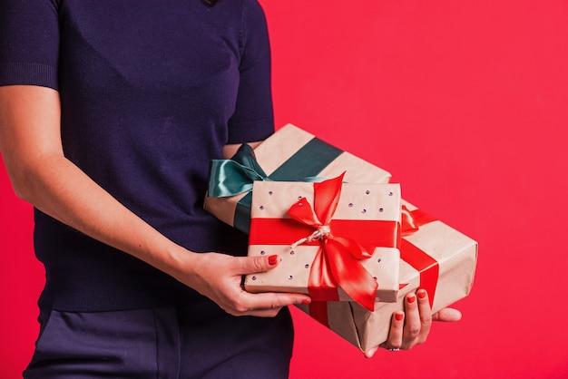 女性の手はスタジオピンクの背景で3つのプレゼントを保持します