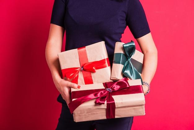 Руки женщины держат три подарка в студии розовом фоне