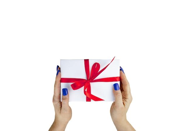 女性の手は白いテーブルで隔離の上面図の赤いリボンと白い色のギフトプレゼントボックスを保持します。クローズアップ、上面図。選択的なソフトフォーカス。テキストコピースペース。休日のコンセプト