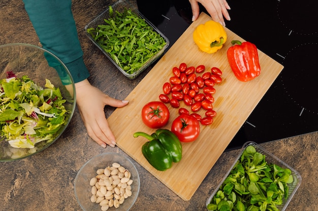 여자 손 잡고 나무도 마, 신선한 야채 rucola, 체리 토마토, 고추와 샐러드 요리. 평면도. 건강한 채식 음식 개념