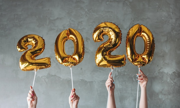 The woman hands holding 2020 numbers balloons on grey concrete wall background