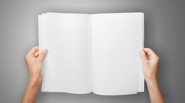 灰色の背景にコピースペースを持つ読者のための空白の本を保持している女性の手