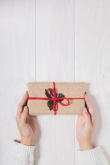 白い木製の背景にクリスマスプレゼントを保持している女性の手
