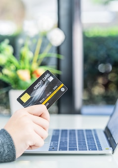 オンラインショッピングのためのクレジットカードを保持している女性の手