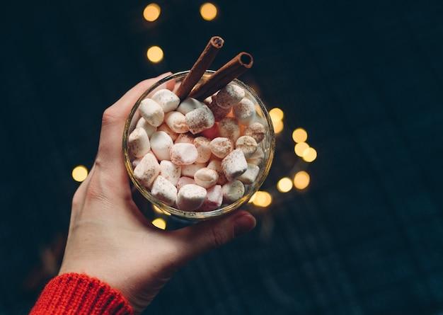 暗いテーブルにシナモンとマシュマロとホットココアのカップを保持している女性の手。クリスマスと新年の背景。上面図。