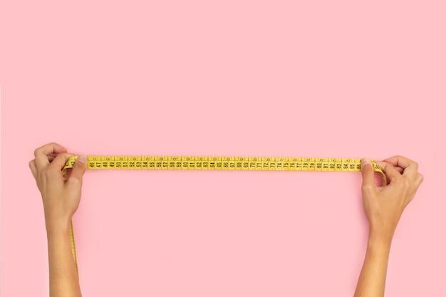 Руки женщины, держа измерительную ленту на розовом фоне
