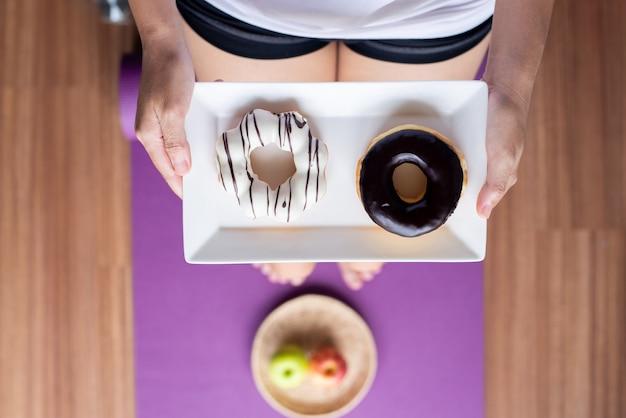 요가 매트에 서서 구운 도넛을 들고 있는 여성의 손, 건강한 식단, 다이어트 개념, 탑 뷰