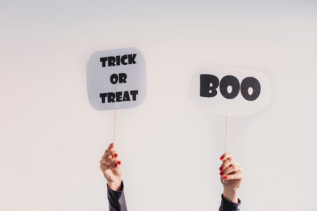 Woman hands holding a boo and a trick or treat sign. wearing a black and white skeleton costume. halloween concept. indoors. lifestyle