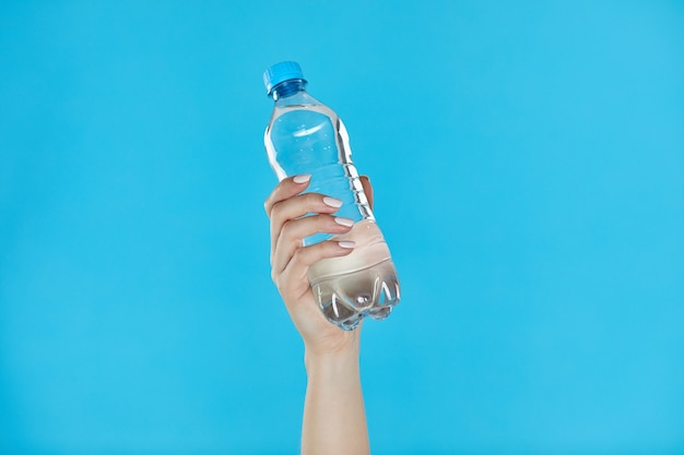 Woman hands holding bottle of water on blue