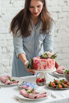 プレートにイチゴの花とケーキを保持している女性の手