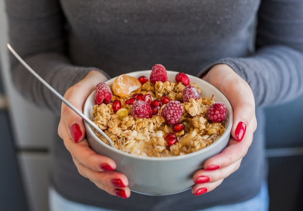 Woman hands holding cereal and fruit bowl
